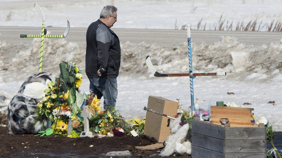 Myles Shumlanski looks around a makeshift memorial at the intersection of a fatal bus crash near Tisdale, Sask., Tuesday, April, 10, 2018. (Jonathan Hayward / THE CANADIAN PRESS)