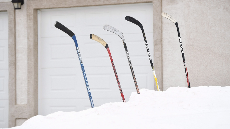 Hockey sticks sit in a snow bank in front of a house in Humboldt, Sask., on Monday, April 9, 2018. (THE CANADIAN PRESS/Jonathan Hayward)