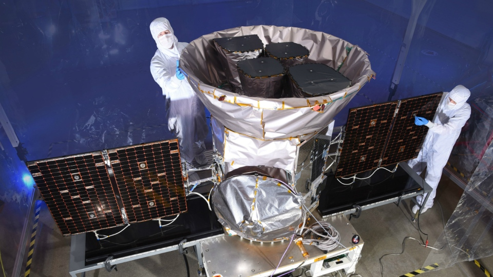 Technicians are seen working with the Transiting Exoplanet Survey Satellite (TESS) in this undated image. (NASA via AP)