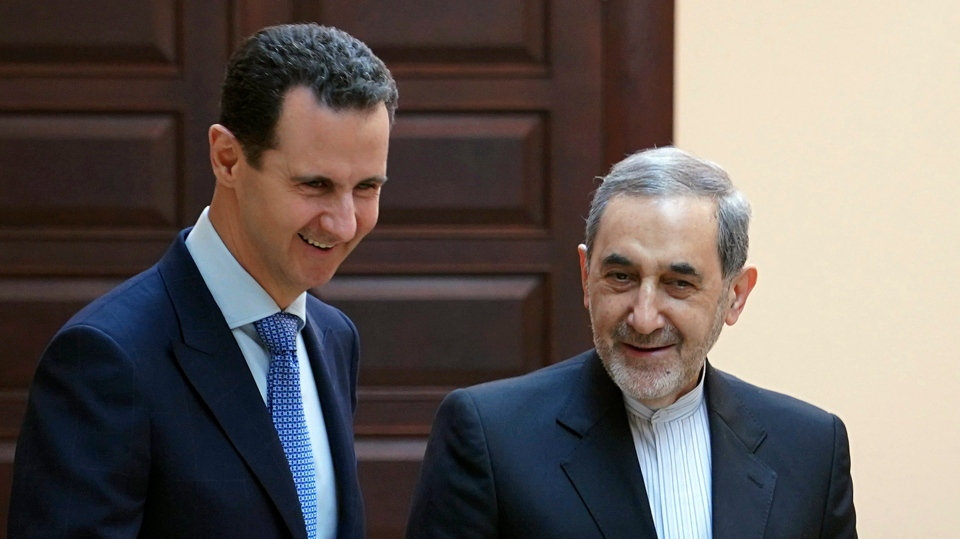 In this photo released by the Syrian official news agency SANA, Syrian president Bashar Assad, left, meets with Ali Akbar Velayati, an adviser to Iran's Supreme Leader Ayatollah Ali Khamenei, in Damascus, Syria, Thursday, April 12, 2018. (SANA via AP)