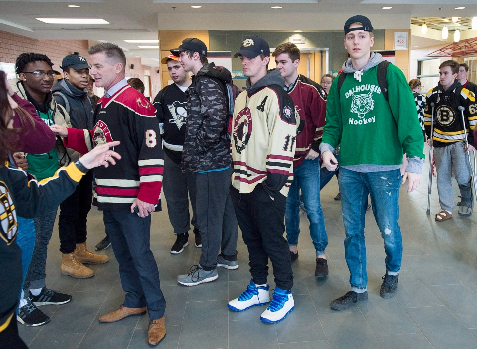 Citadel High School principal Joe Morrison, left, chat with students as they wear sports jerseys to honour the victims of the Humboldt Broncos bus crash in Halifax on Thursday, April 12, 2018. (THE CANADIAN PRESS/Andrew Vaughan)