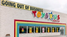 """A """"Going Out Of Business"""" sign hangs over the Toys """"R"""" Us store logo in Omaha, Neb., Monday, April 9, 2018. (THE CANADIAN PRESS/AP/Nati Harnik)"""