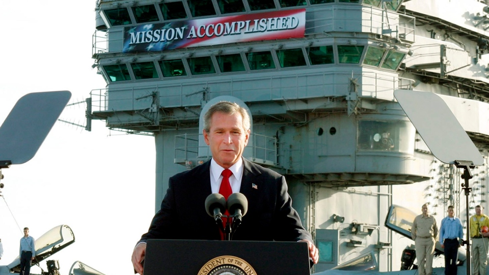 FILE - In this May 2, 2003 file photo, President George W. Bush declares the end of major combat in Iraq as he speaks aboard the aircraft carrier USS Abraham Lincoln off the California coast. As he declares the U.S.-led airstrikes against Syria a success, President Donald Trump is adopting a phrase that a previous president came to regret. (AP Photo/J. Scott Applewhite, File)
