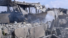 Syrian fireman extinguishes smoke after airstrikes