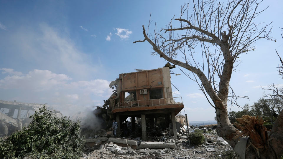 A fireman extinguishes smoke that rises from the damage of the Syrian Scientific Research Center which was attacked by U.S., British and French military strikes to punish President Bashar Assad for suspected chemical attack against civilians, in Barzeh, near Damascus, Syria, Saturday, April 14, 2018. (AP Photo/Hassan Ammar)