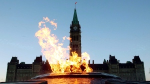 The Centre Block of the Parliament Buildings is shown through the Centennial Flame on Parliament Hill in Ottawa on Sunday, January 25, 2015. (THE CANADIAN PRESS/Fred Chartrand)