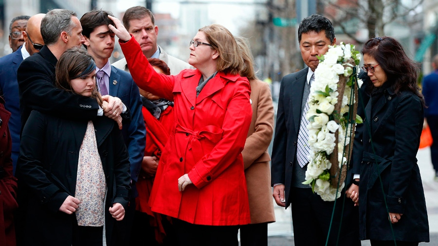 The father of Lingzi Lu, Jun Lu, second from right, and her aunt Helen Zhao, right, observe a moment of silence with the family of Martin Richard, foreground from left, Bill, Jane, Henry and Denise, during a ceremony at the site where Martin Richard and Lingzi Lu were killed in the second explosion at the 2013 Boston Marathon, Sunday, April 15, 2018, in Boston. (AP Photo/Michael Dwyer)