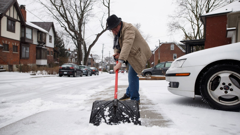 A man shovels his sidewalk during a spring storm in Toronto on Saturday, April 14, 2018. THE CANADIAN PRESS/Cole Burston
