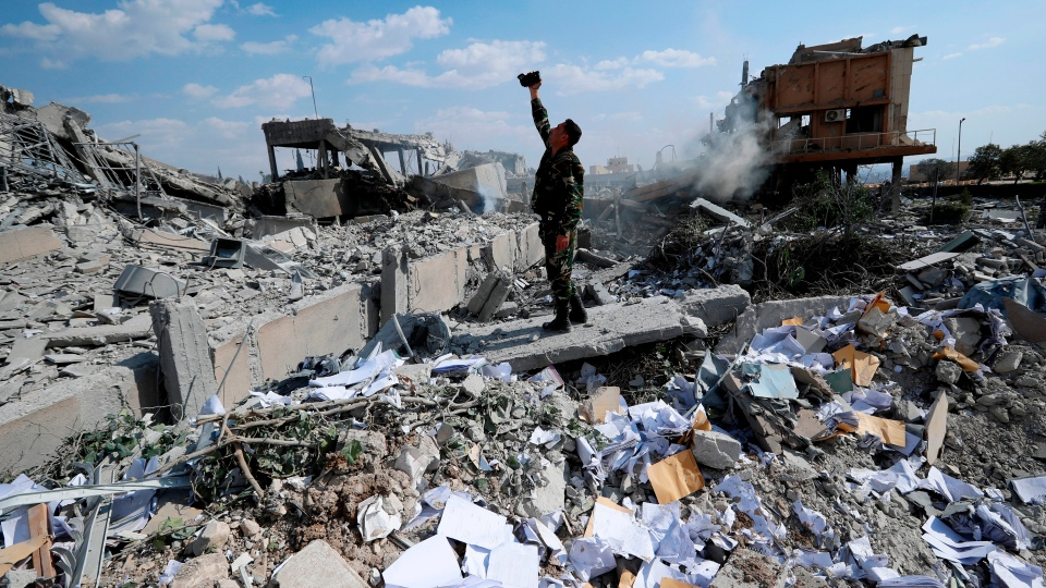 FILE - In this Saturday, April 14, 2018 file photo, a Syrian soldier films the damage of the Syrian Scientific Research Center which was attacked by U.S., British and French military strikes to punish. (AP Photo/Hassan Ammar, File)