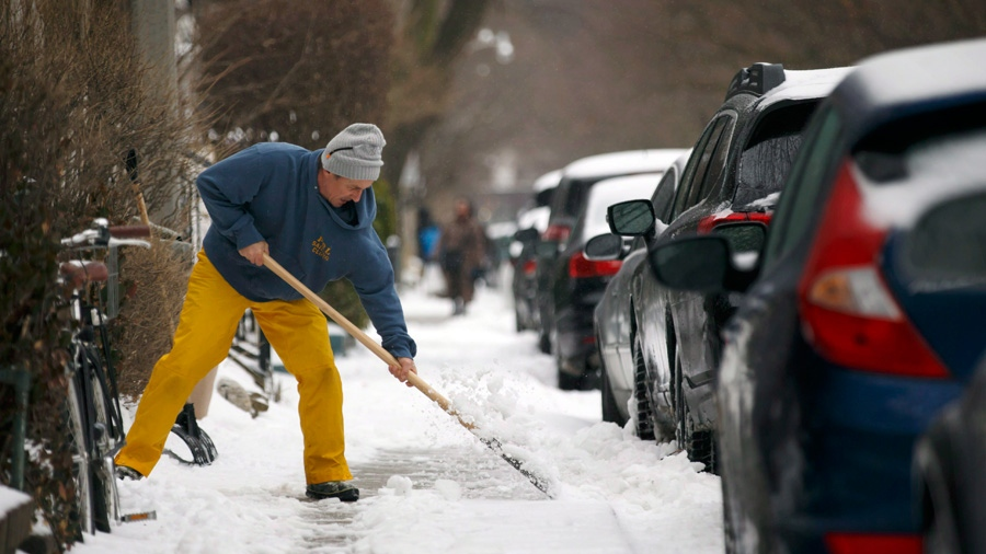 Stefan Randstrom clears ice from his sidewalk in Toronto, Ontario as a mix of snow, hail, and rain fall on Sunday, April 15. 2018. (THE CANADIAN PRESS/Cole Burston)