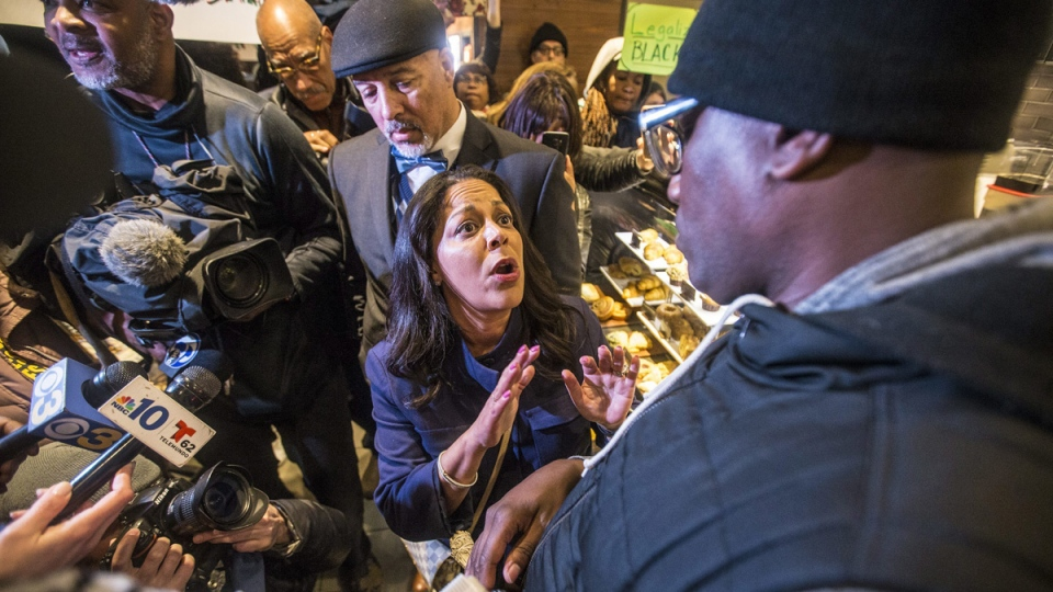 Camille Hymes, centre, regional vice president of Mid-Atlantic operations at Starbucks Coffee Company, speaks with Asa Khalif, of Black Lives Matter, right, on April 15, 2018. (Mark Bryant / The Philadelphia Inquirer via AP)