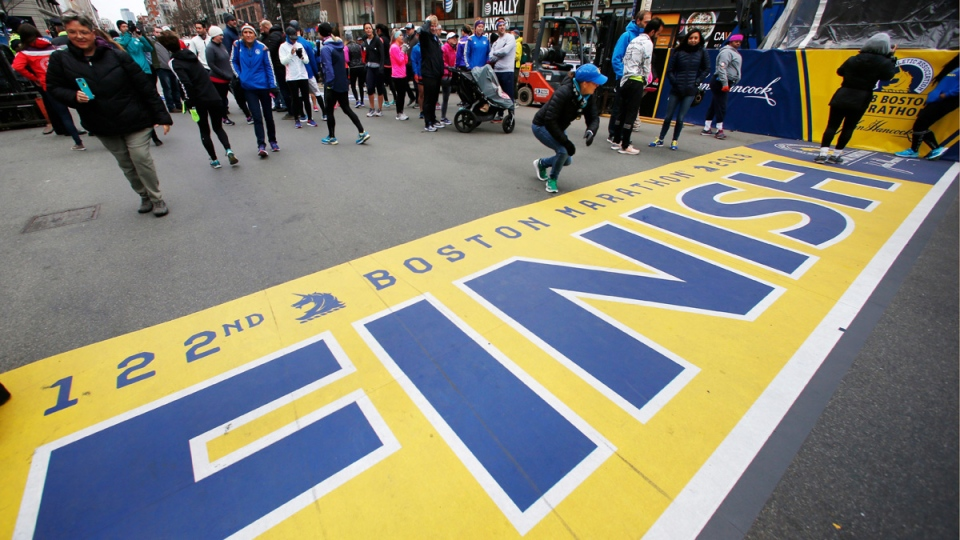 People gather at the Boston Marathon finish line in Boston, Sunday, April 15, 2018 ahead of Monday's race. (AP Photo/Michael Dwyer)