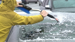 An Ottawa resident cleans ice off the windshield of a car after rain coated the city in a layer of ice mid April, 2018.