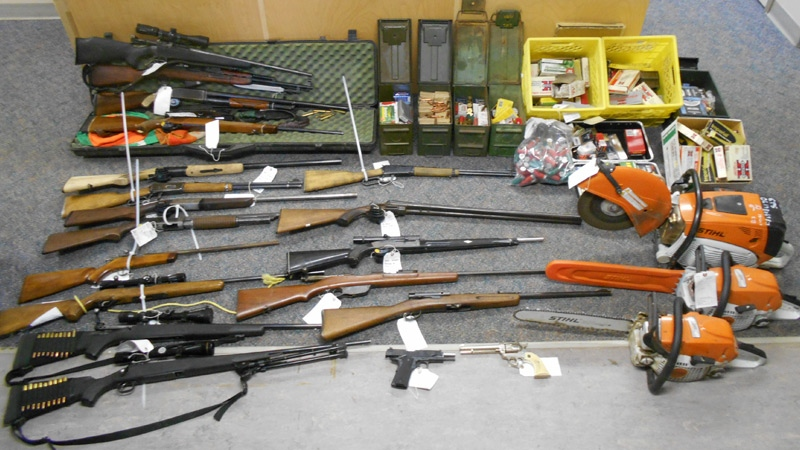 A loaded handgun, 21 long-barreled firearms, and thousands of rounds of ammunition were seized in one of the search warrants. (Supplied)