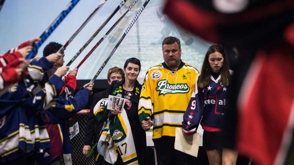 Scott Thomas, centre, walks with his family through the honour guard during the funeral of his son and Humboldt Broncos player Evan Thomas in Saskatoon on Monday, April, 16, 2018. THE CANADIAN PRESS/Kayle Neis