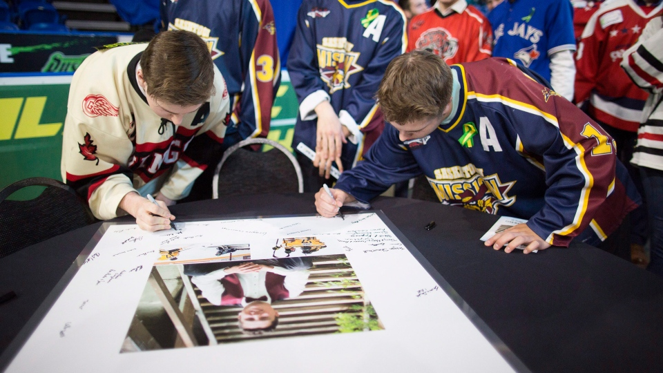 Attendants sign a poster of Evan Thomas during the funeral for the Humboldt Broncos player in Saskatoon on Monday, April, 16, 2018. THE CANADIAN PRESS/Kayle Neis