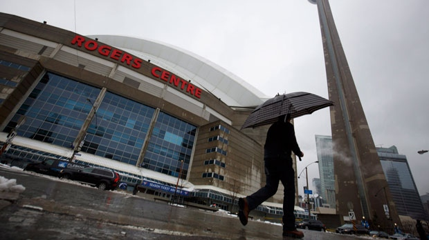 A man walks by the Rogers Centre as reports of falling ice from the CN Tower sparked a closure of parts of the area on Toronto on Monday, April 16, 2018. (THE CANADIAN PRESS/Cole Burston)