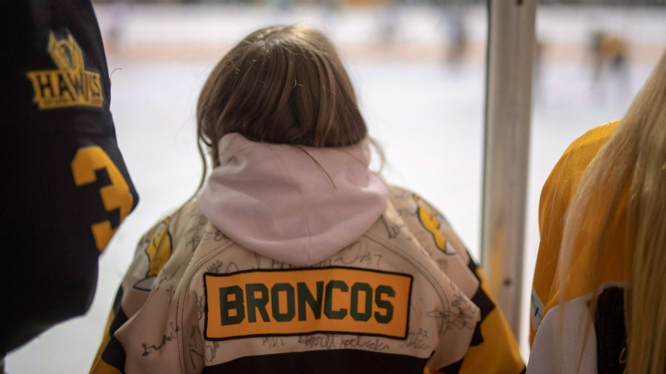 "A fan wears a Nipawin Hawks jersey with ""Broncos"" on the name bar as tribute to the Humboldt Broncos during game one of the Saskatchewan Junior Hockey league finals between the Estevan Bruins and Nipawin Hawks in Nipawin, Sask. on Saturday, April 14, 2018. (THE CANADIAN PRESS/Liam Richards)"