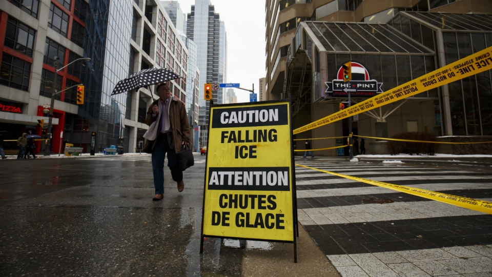 A man walks by the foot of John Street as an area around the CN Tower is closed off due to reports of falling ice in Toronto on Monday, April 16, 2018. THE CANADIAN PRESS/Cole Burston