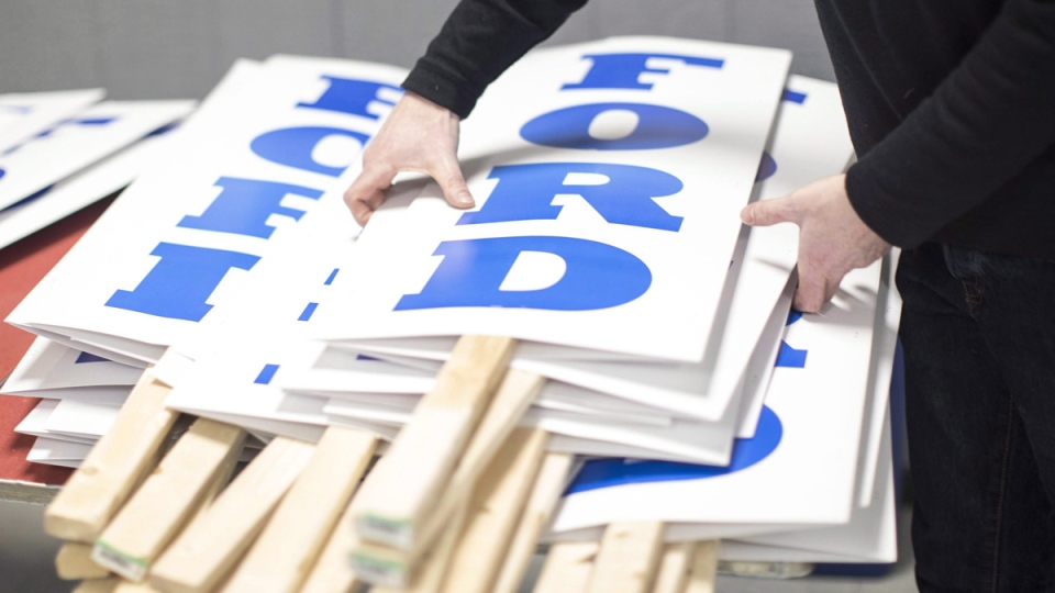 A campaign aide gathers signs before a campaign rally by Ontario PC Leader Doug Ford in Oshawa, Ontario, on March 24, 2018. (Chris Young /THE CANADIAN PRESS)