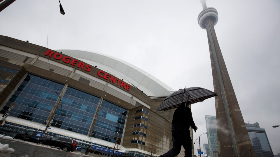 A man walks by the Rogers Centre as reports of falling ice from the CN Tower sparked a closure of parts of the area on Toronto on Monday, April 16, 2018. THE CANADIAN PRESS/Cole Burston