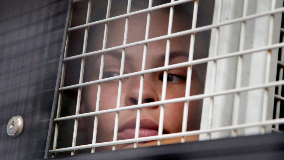 Anastasia Vashukevich sits inside a prison transport vehicle outside a courthouse in Pattaya, south of Bangkok, Thailand, Tuesday, April 17, 2018. (AP Photo/Gemunu Amarasinghe)
