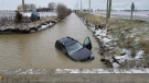 A vehicle slid into a ditch full of water on Lighthouse Road and Tecumseh Road in Lakeshore, Ont., Tuesday, April 17, 2018. (Courtesy OPP)