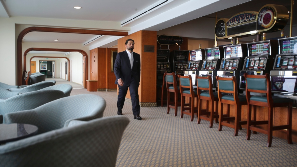 Hamza Mustafa, the CEO of Dubai' Aos Ports, Customs and Free Zone Corp.' passes slot machines that will remain turned off as gambling is illegal, aboard the Queen Elizabeth 2, moored off the Mideast city-state of Dubai, United Arab Emirates, Tuesday, April 17, 2018. (AP Photo/Kamran Jebreili)