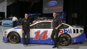 Driver Clint Bowyer poses with a new Ford Fusion, on Jan. 18, 2017. (Chuck Burton / AP)