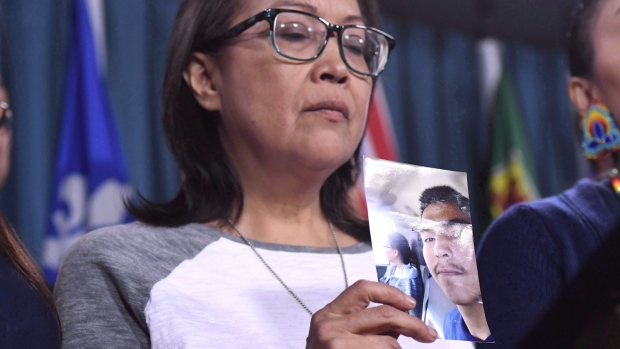 In this file photo, Debbie Baptiste, mother of Colten Boushie, holds a photo of her son during a press conference on Parliament Hill in Ottawa on February 14, 2018.  THE CANADIAN PRESS/Justin Tang
