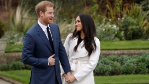 FILE - In this file photo dated Monday Nov. 27, 2017, Prince Harry and his fiancee Meghan Markle pose for photographers in the grounds of Kensington Palace in London, following the announcement of their engagement. (AP Photo/Matt Dunham)