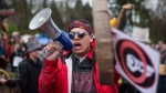 FILE -- Cedar George-Parker addresses the crowd as protesters opposed to the Kinder Morgan Trans Mountain pipeline extension defy a court order and block an entrance to the company's property, in Burnaby, B.C., on April 7, 2018. (THE CANADIAN PRESS/Darryl Dyck)