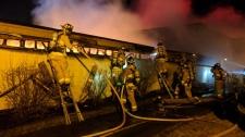 Firefighters battle a blaze in an overnight fire where 25 cars have been damaged in Ottawa's Bayshore neighbourhood. (@OFSFirePhoto/Twitter)