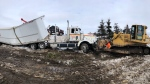 Heavy construction equipment is used to remove a tractor trailer from a ditch along Highway 400 south of Barrie, Ont.