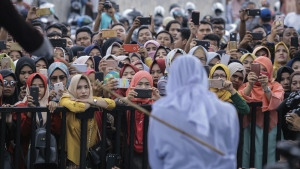 People use their mobile phones to take pictures as a Shariah law official whips a woman who is convicted of prostitution during a public caning outside a mosque in Banda Aceh, Indonesia, Friday, April 20, 2018. (AP Photo/Heri Juanda)