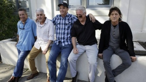In this Friday, April 13, 2018, photo, the Waldos, from left, Mark Gravitch, Larry Schwartz, Dave Reddix, Jeffrey Noel and Steve Capper sit on a wall they used to frequent at San Rafael High School in San Rafael, Calif.  (AP /Eric Risberg)
