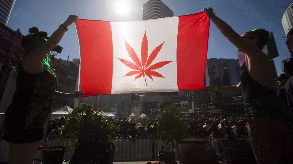 Two people hold a modified design of the Canadian flag with a marijuana leaf in in place of the maple leaf during the