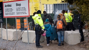 A family is arrested by RCMP officers as they cross the border into Canada from the United States as asylum seekers on Wednesday, April 18, 2018 near Champlain, NY. (THE CANADIAN PRESS/Paul Chiasson)
