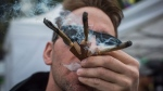 Brandon Bartelds smokes three joints at once while attending the 4/20 annual marijuana celebration, in Vancouver, B.C., on Friday April 20, 2018. THE CANADIAN PRESS/Darryl Dyck
