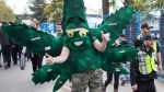 Police officers walk past a man wearing a marijuana leaf mascot costume during the 4/20 annual marijuana celebration, in Vancouver, B.C., on Friday April 20, 2018. THE CANADIAN PRESS/Darryl Dyck