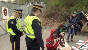 Police look on as demonstrators protest the Kinder Morgan pipeline expansion in Burnaby, B.C. on Friday, April 20, 2018. (Steve Saunders / CTV Vancouver)
