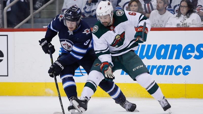 Winnipeg Jets' Andrew Copp (9) steals the puck from Minnesota Wild's Ryan Murphy (6) during second period game five NHL playoff action in Winnipeg on Friday, April 20, 2018. THE CANADIAN PRESS/John Woods