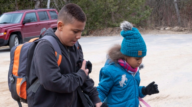 Two young members of a family from Colombia get set to cross the border into Canada from the United States as asylum seekers on Wednesday, April 18, 2018 near Champlain, NY. THE CANADIAN PRESS/Paul Chiasson
