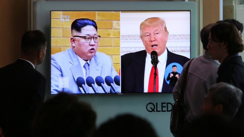 People watch a TV screen showing file footage of U.S. President Donald Trump, right, and North Korean leader Kim Jong Un during a news program at the Seoul Railway Station in Seoul, South Korea, Saturday, April 21, 2018. (AP Photo/Ahn Young-joon)