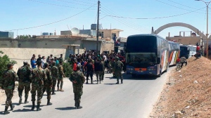 This photo released by the Syrian official news agency SANA, shows Syrian government forces overseeing the evacuation by bus of rebels and their family from the towns of Ruhaiba in the eastern Qalamoun region in the Damascus countryside, Syria, Saturday, April 21, 2018. (SANA via AP)