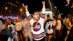 Winnipeg Jet fans celebrate at Portage an Main in downtown Winnipeg after the Winnipeg Jets defeated the Minnesota Wild in game five NHL playoff action to win the first round 4-1 in Winnipeg on Friday, April 20, 2018. (THE CANADIAN PRESS/John Woods)