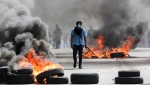 A masked protester walks between burning barricades in Managua, Nicaragua, Friday, April 20, 2018. (AP Photo/Alfredo Zuniga)