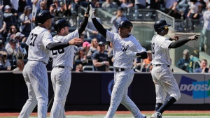 New York Yankees center fielder Aaron Hicks, center, celebrates with Giancarlo Stanton (27) and Austin Romine (28) after scoring on a bases loaded double by Miguel Andujar during the sixth inning of a baseball game against the Toronto Blue Jays, Saturday, April 21, 2018, in New York. (AP Photo/Julie Jacobson)