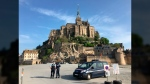 Police attend the scene of an evacuation at Mont Saint-Michel, on France's northern coast, Sunday April 22, 2018. (Denis Surfys via AP)
