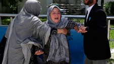 A woman shouts and cries at a hospital after she lost her son in a suicide attack on a voter registration center in Kabul, Afghanistan, Sunday, April 22, 2018. Gen. Daud Amin, the Kabul police chief, said a suicide bomber targeted civilians who had gathered to receive national identification cards. (AP Photo/Massoud Hossaini)